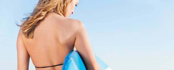 girl on the beach holding surfering board