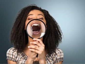 girl showing her teeth with magnifying glass