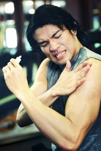 man rubbing arm in pain
