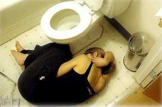 woman lying down by the toilet upset stomach