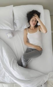 girl with heachache on bed