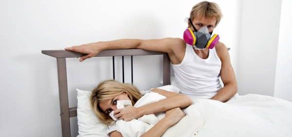 man wearing mask while sick woman on the bed