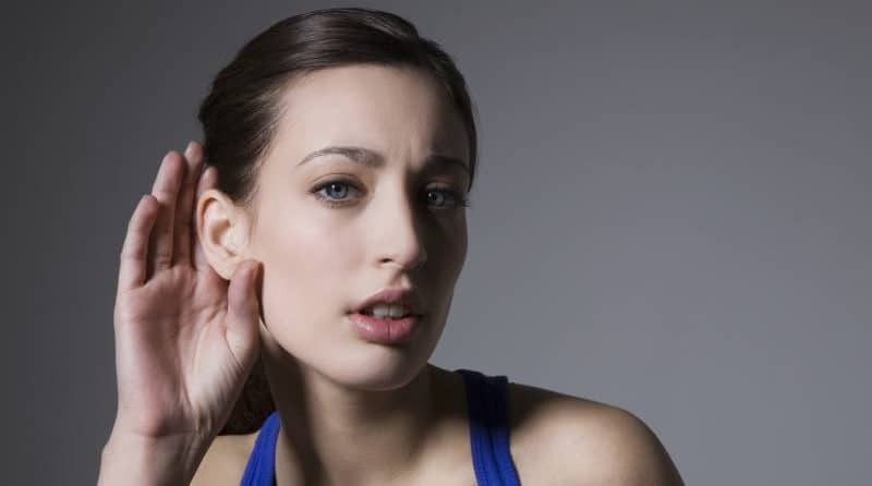 girl holding ears