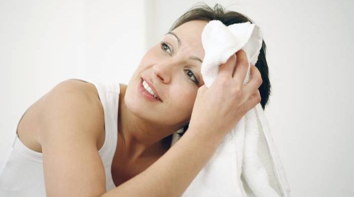 woman holding towel on forehead