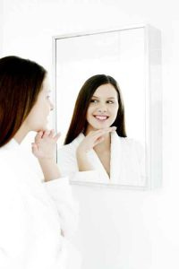 woman watchng her skin in the mirror