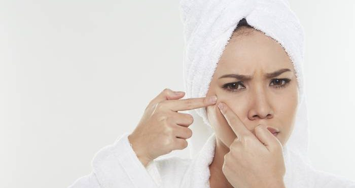 woman squeezing her pimple