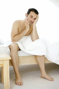 man in towel on bed