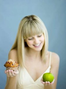 woman holding apple and muffin