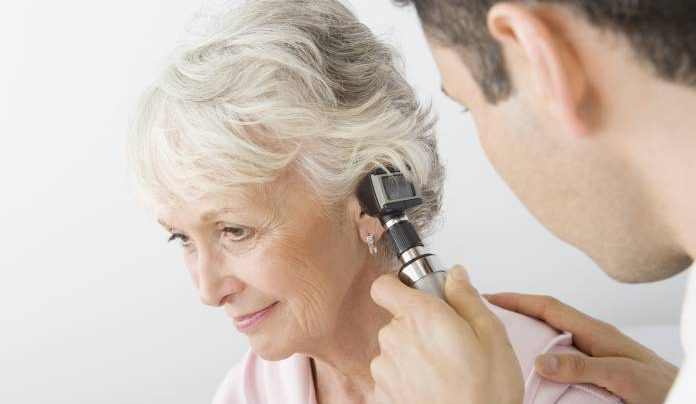doctor checking woman ear